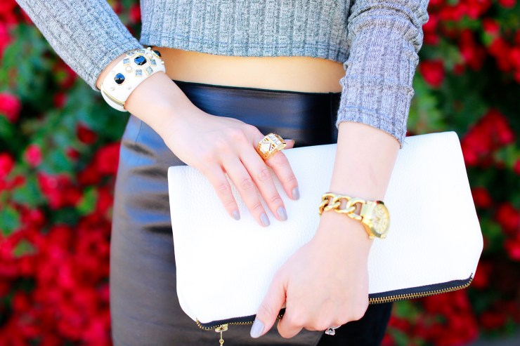 An Dyer wearing White Leather Clutch with Isharya Ring and Express Watch