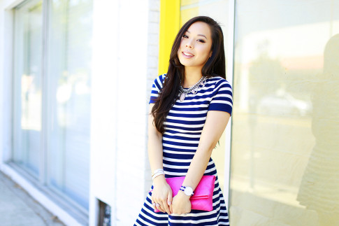 An Dyer wearing Navy Stripe Cap Sleeve carrying Chanel Hot Pink Foldover Clutch