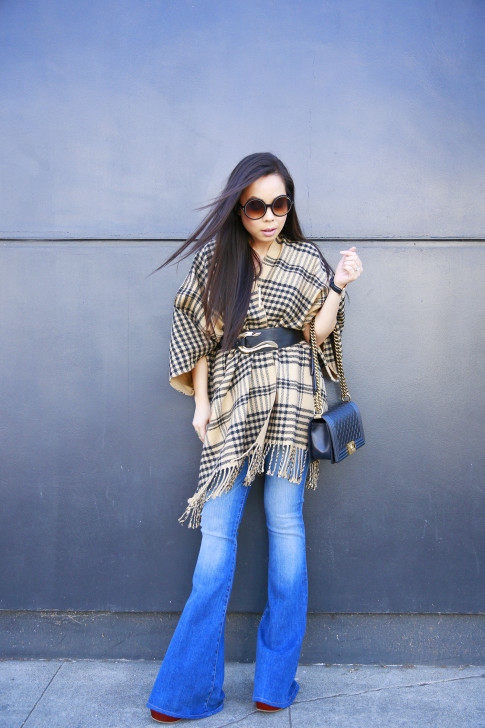 An Dyer wearing Hudson Mia Flares, Morning Lavender Poncho with Marciano Belt and Chanel Boy Bag
