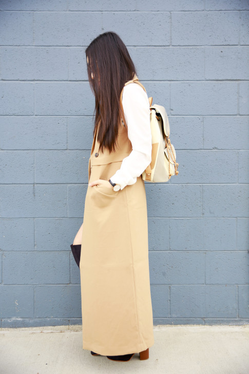 An Dyer wearing long tan trench coat sleeveless duster