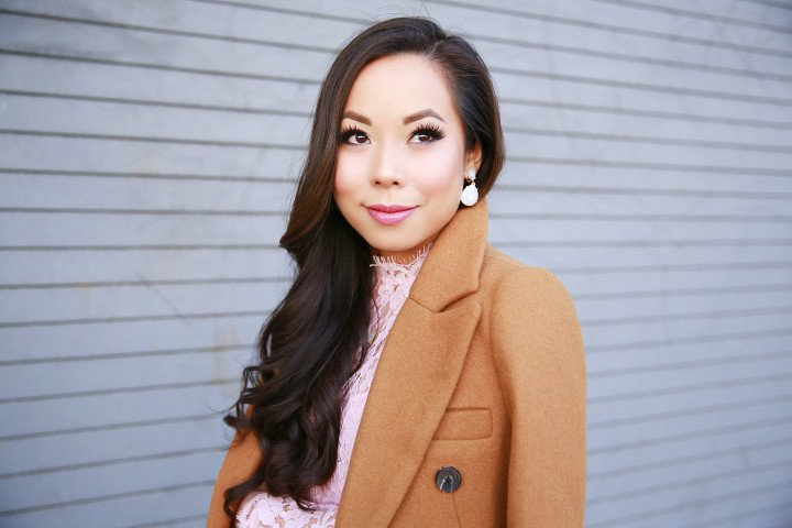 An Dyer wearing Charming Charlie Pearl Ivory Clip On Dangly Earrings with Camel Coat over the shoulders