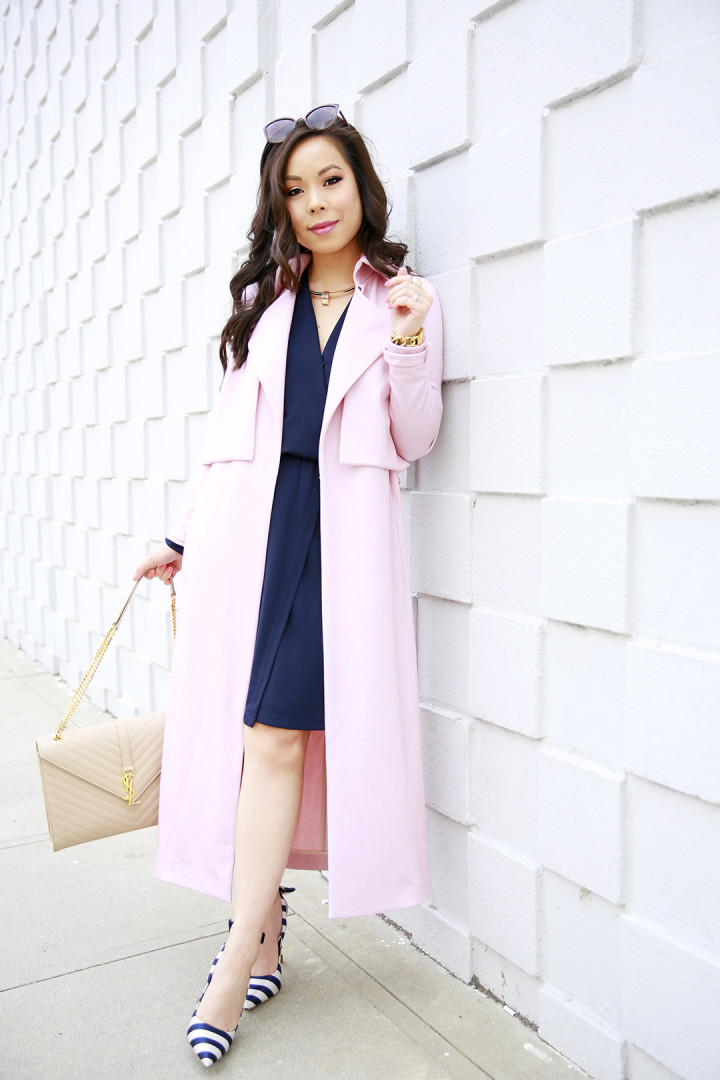 An Dyer wearing LXE Riverside Trench Blush Pink Duster Coat, Navy Wrap Dress and Navy Stripe Bow Slingback Pumps