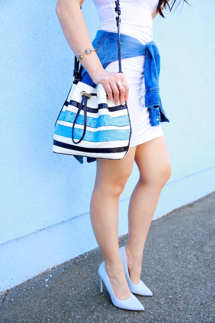 An Dyer wearing Call it Spring Light Blue Pumps with Brahmin Blue Stripe Bucket Bag