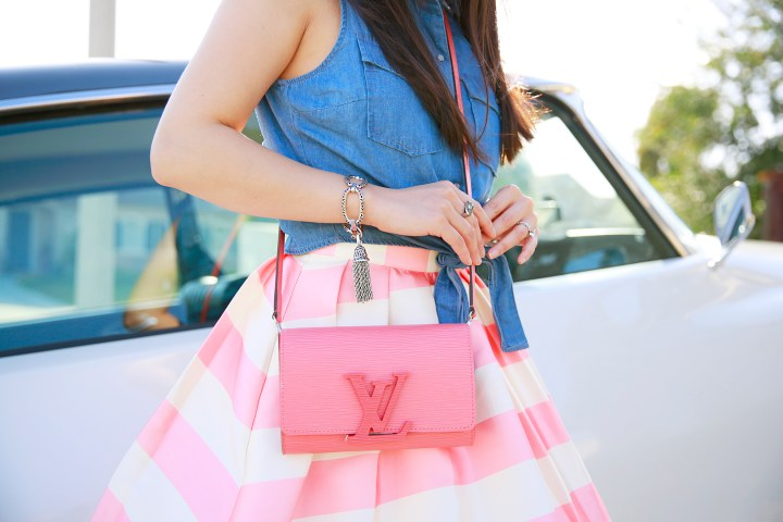 An Dyer wearing Kendra Scott Tassel Bracelet with Louis Vuitton Louise Corail Clutch