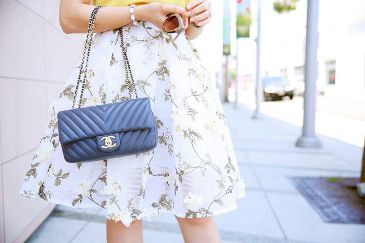 An Dyer wearing Chanel Chevron Flap with Chicwish Floral Applique Midi SKirt