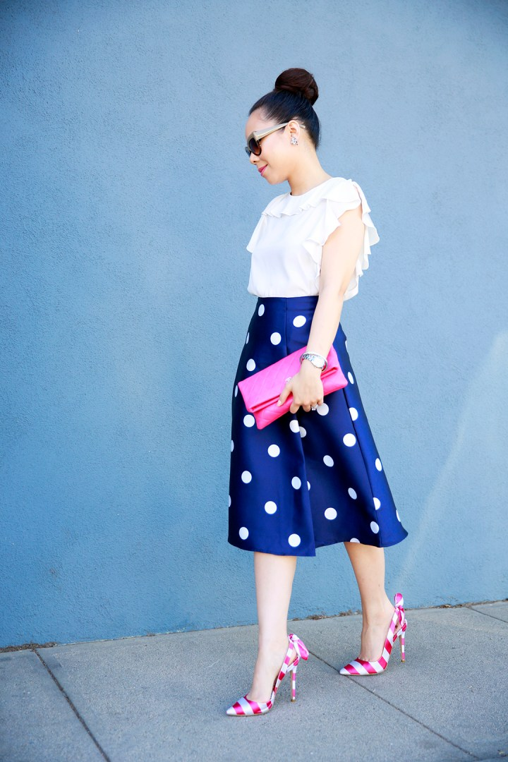 An Dyer wearing Chanel Pink Quilted Foldover Clutch, Amanda Uprichard Ruffled Top with Navy Polka Dot Skirt and Pink Striped Bow Pumps