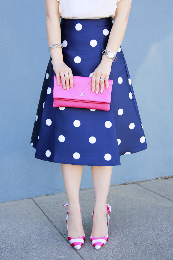 An Dyer wearing Charming Charlie accessories, chanel pink foldover clutch, pink striped bow pumps and navy polka dot skirt