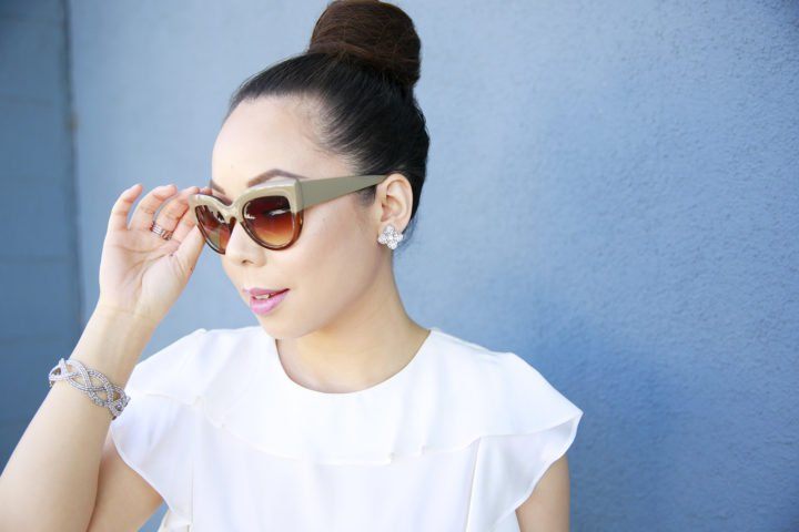 An Dyer wearing Charming Charlie clip-on earrings, sunglasses and bracelet