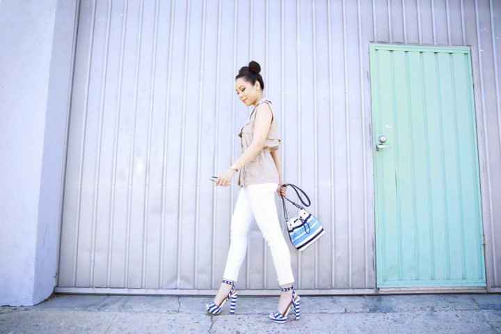 An Dyer wearing Trench Vest with White jeans and Navy Striped Platform Sandals