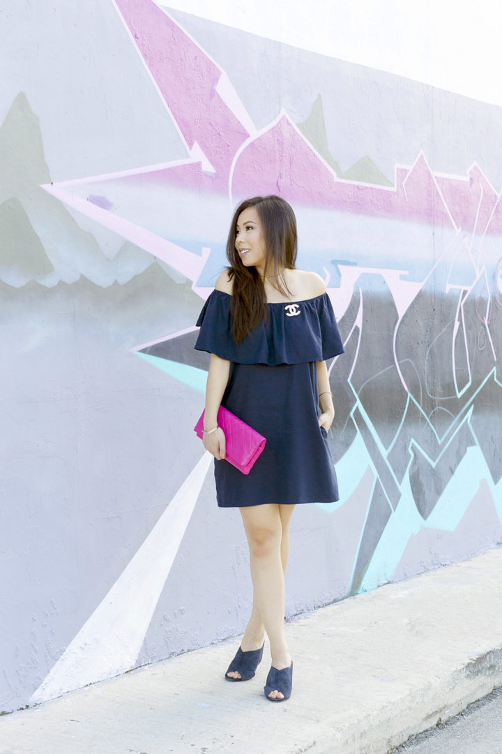 an-dyer-wearing-chanel-brooch-and-clutch-navy-off-shoulder-dress-suede-mules-in-fat-art-district-fort-lauderdale-street-style-pink-mural