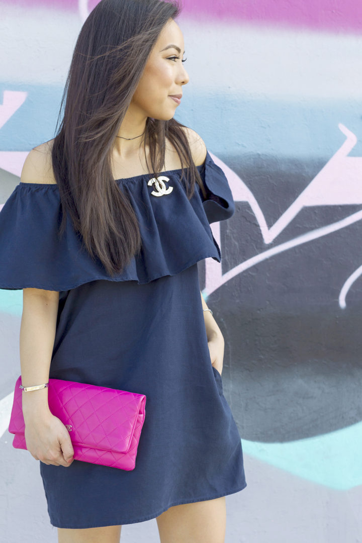 an-dyer-wearing-chanel-brooch-with-chanel-clutch-and-off-shoulder-navy-dress-fort-lauderdale-street-style-florida