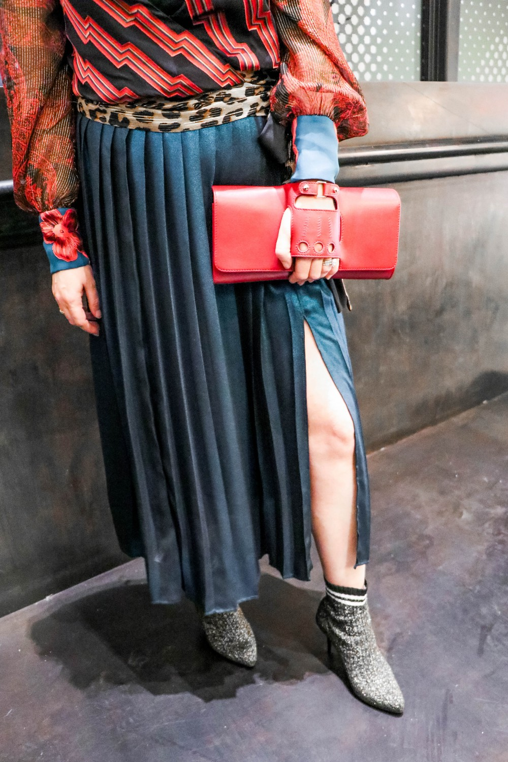 Wearing a Blue Metallic Pleated Midi Skirt for NYFW. Click on the photo to read the blog post + get outfit details! #NYFW #NYFWstreetstyle #aliceandolivia #topshop #stuartweitzman #sockbooties