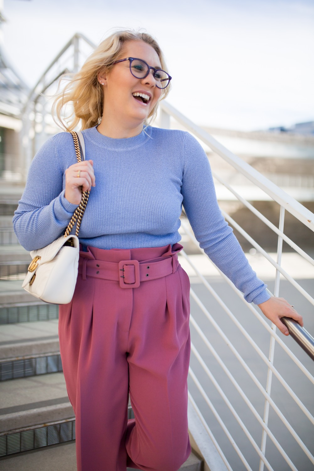 girl laughing wearing glasses a blue sweater and pink pants