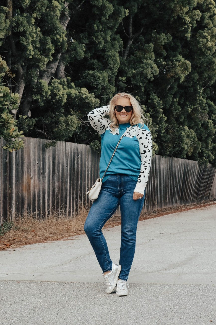Casual outfit wearing a leopard sleeve sweater, jeans, and sneakers. #casualoutfit #leopardprint #sweateroutfit