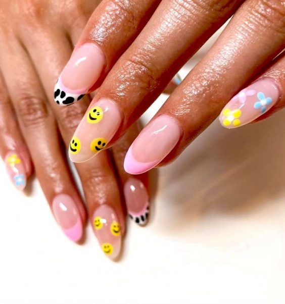 Mismatched nail art trend with smily faces flowers and cow print