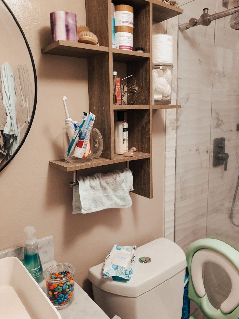 Apothecary jars are great for storing small bathroom essentials like qtips and cotton balls or m&ms if you're potty training like we are. Head to the post to check out the other top 20 storage solutions I use to keep my house looking as decluttered as possible. #homeorganization #ApothecaryJars #bathroomorganization