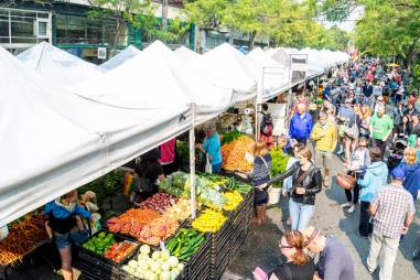 Visiting a local farmers market to source fresh vegetables