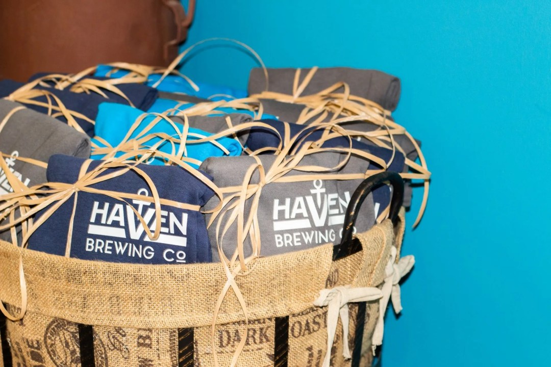 Picture of basket full of blue and grey Haven-branded t-shirts.