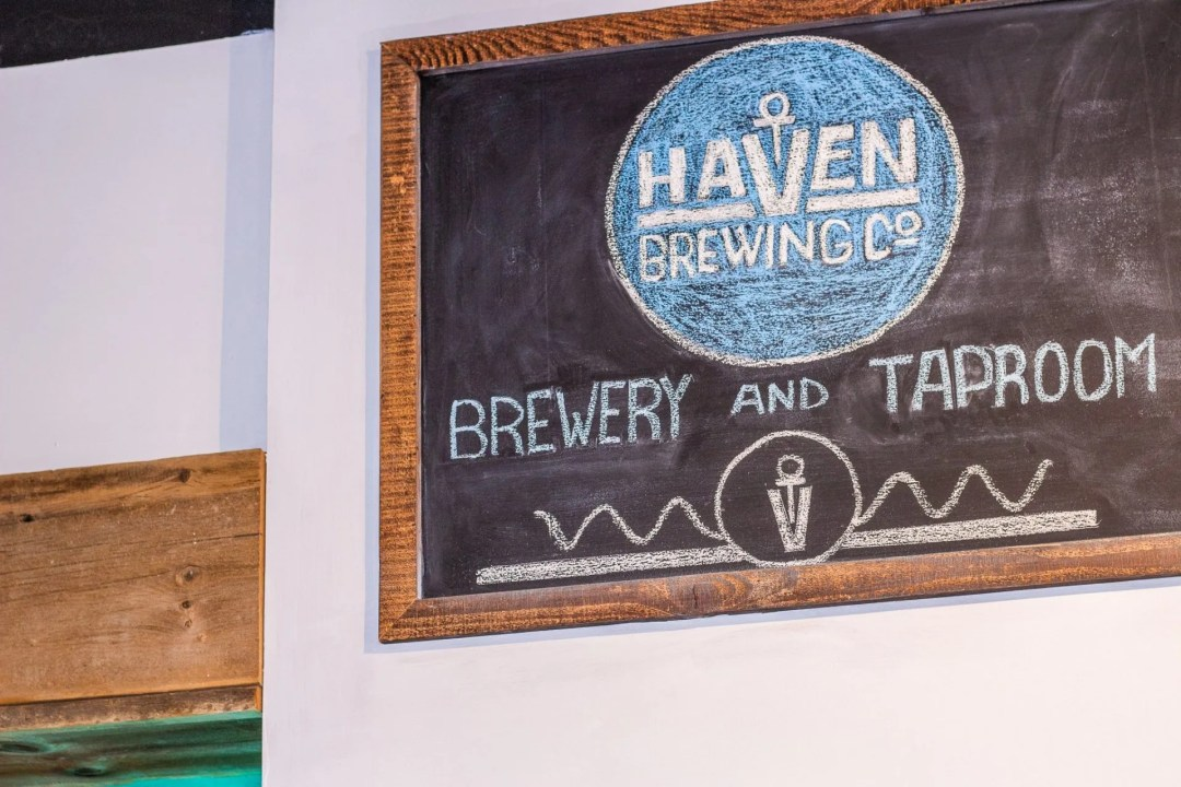 """Closeup of chalk board with Haven logo and writing """"taproom"""""""