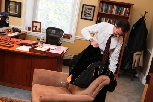 Weiss prepares to don an academic robe in his office in Founders Hall before attending his Inaugural Ceremony.