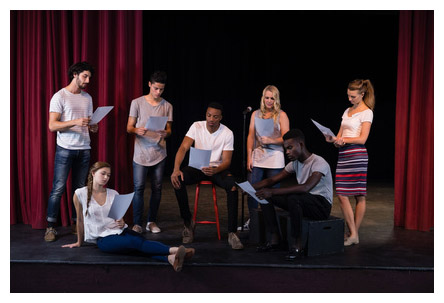 students reading play script on stage
