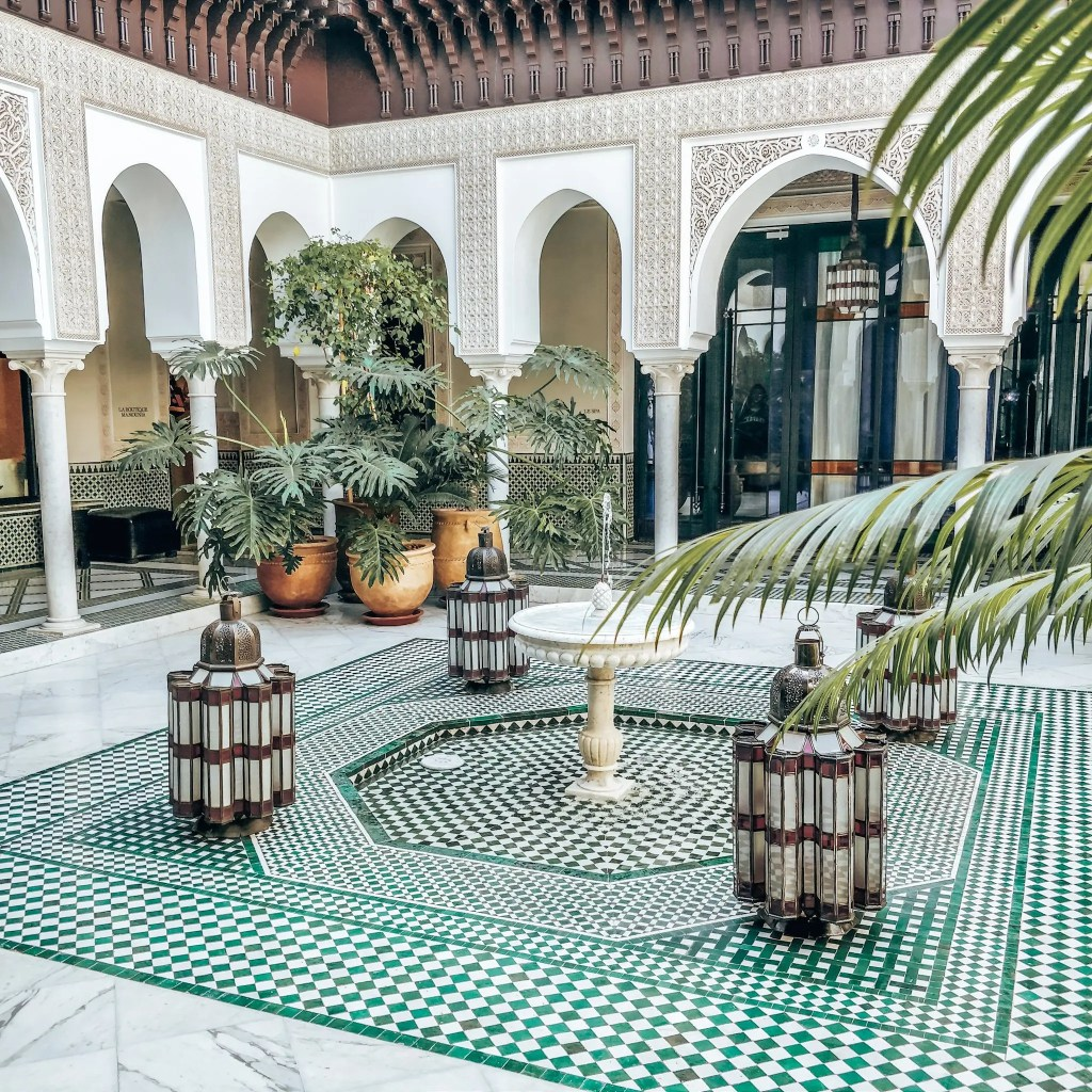 An open courtyard surround by columns. A fountain in the middle surrounded by colourful tiles.