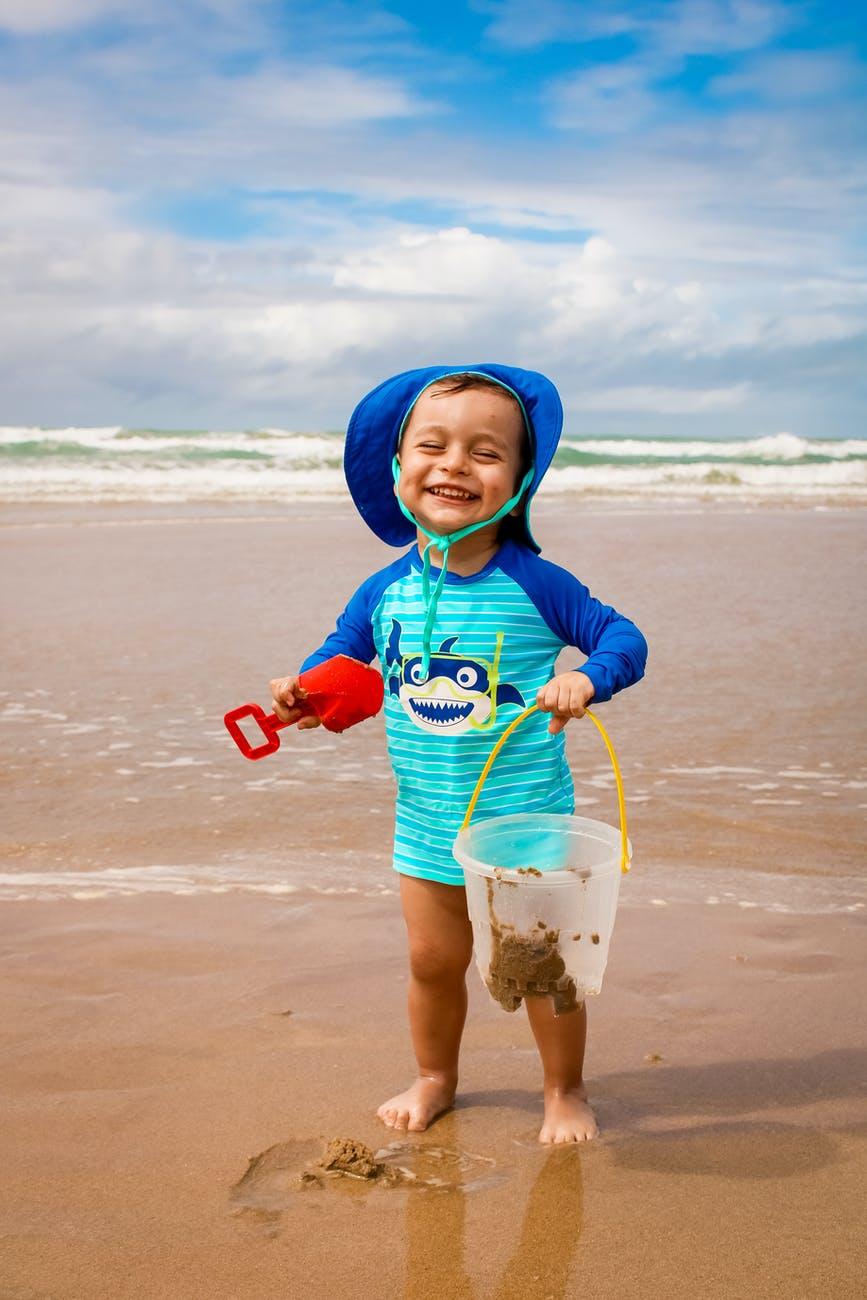 photo of kid playing on seashore