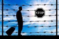 Concept of refugee. Silhouette of a refugee with a bag on a background of a fence with barbed wire and stop sign