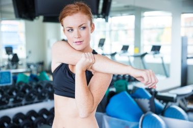 Pretty woman with red hair stretching before workout in gym
