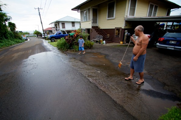 A resident downhill from the damaged pipe sweeps away mud and debris washing down the roadway. Photography by Baron Sekiya   Hawaii 24/7