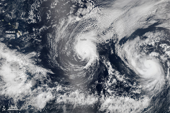 On August 5 2014, the Visible Infrared Imaging Radiometer Suite (VIIRS) sensor on Suomi-NPP captured natural-color images of both Iselle and Hurricane Julio en route to Hawaii. The image above is a composite of three satellite passes over the tropical Pacific Ocean in the early afternoon. Note that Iselle's eyewall had grown less distinct; the storm had descreased to category 2 intensity. The bright shading toward the center-left of the image is sunglint, the reflection of sunlight off the water and directly back at the satellite sensor. NASA image by Jeff Schmaltz, LANCE/EOSDIS Rapid Response.