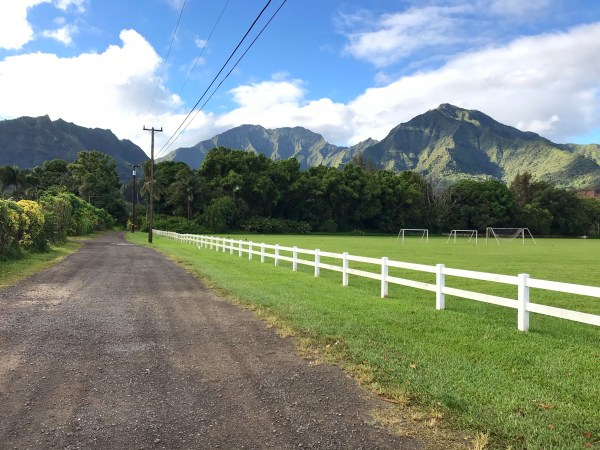 The gravel road leading to the Hanalei farmers market along a white wood fence, grassy field, and dramatic mountain ridge lines.