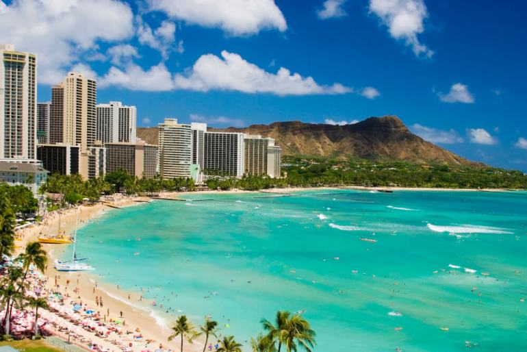 When planning a Hawaii trip, you'll need to decide between a hotel vs condo. Image of Waikiki beach and its hotels.