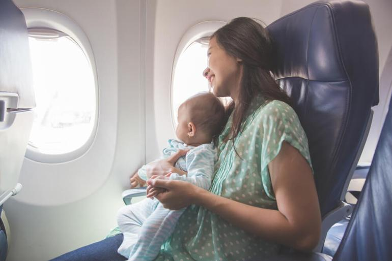 Find out my top tips for flying to Hawaii with a baby. Image of a mom holding a baby on her lap on an airplane.