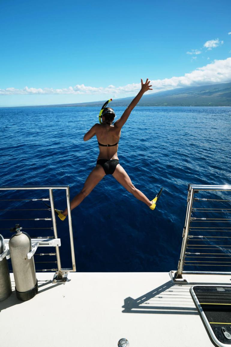 Woman jumping off boat near Molokini Crater in Maui