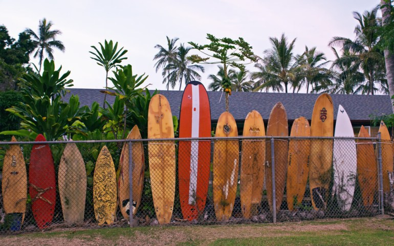 Oahu Surfing On The North Shore, a complete guide featured by top Hawaii blog, Hawaii Travel with Kids: A fence lined with surfboards on the North Shore of Oahu, Hawaii