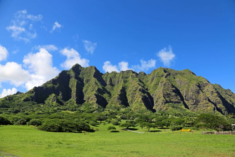 Kualoa Ranch on Oahu is a great stop when Honolulu sightseeing. Image of a green mountain with jagged cliffs.