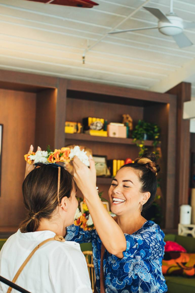 Hawaii Lei Day Celebrations + Activities for Kids featured by top Hawaii blog, Hawaii Travel with Kids: Woman greeting a friend with a lei