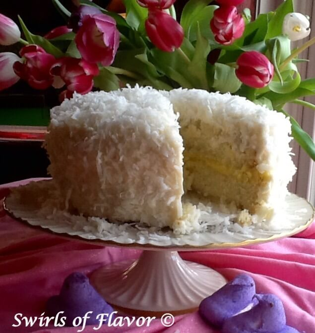 61 Delicious Coconut Dessert Recipes Perfect for Summer featured by top Hawaii blog, Hawaii Travel with Kids: Coconut Lemon Cake is a homemade coconut cake topped with coconut buttercream and flaked coconut. A tangy lemon filling makes every bite heaven!