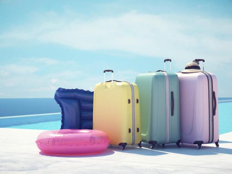 Get your toddler Hawaii Packing List featured by top Hawaii blog, Hawaii Travel With Kids. Image of colorful suitcases and pink inflatable next to the swimming pool