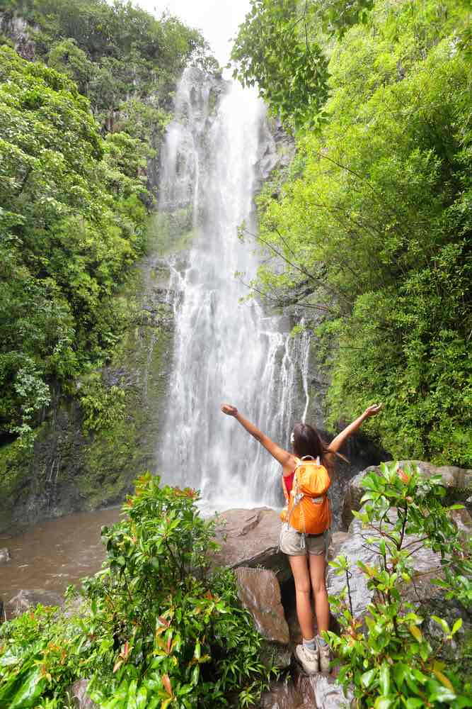 The Road to Hana is a top Maui attraction. Image of a woman wearing an orange backpack standing in front of a waterfall with her arms up.