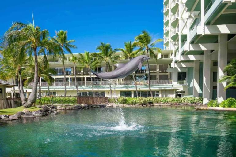 The Kahala Resort and Spa on Oahu is one of the Best Hawaii Hotels for Families. Image of a dolphin jumping in water in front of a hotel.