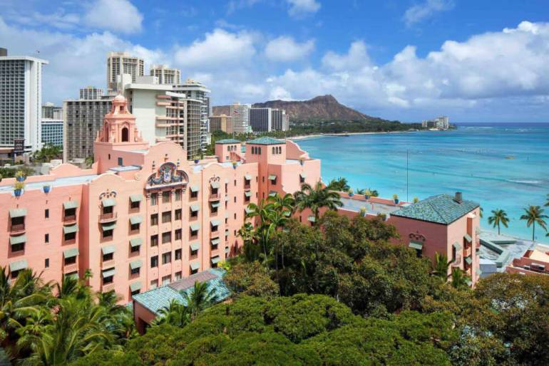 Stay at the Royal Hawaiian Hotel in Waikiki, Oahu with kids. Image of a pink hotel in Waikiki with Diamond Head in the background.
