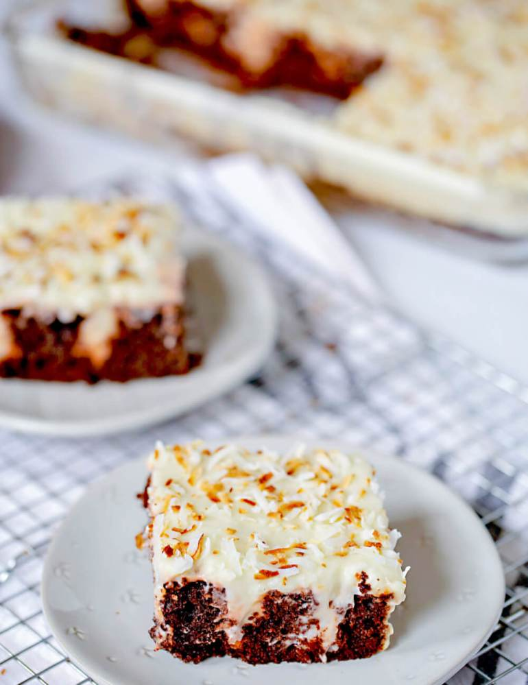 61 Delicious Coconut Dessert Recipes Perfect for Summer featured by top Hawaii blog, Hawaii Travel with Kids: chocolate coconut poke cake slice with toasted coconut