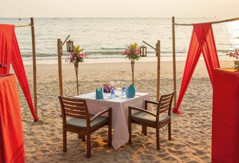 Top 10 Romantic Hawaii Beach Proposal Ideas + Locations featured by top Hawaii blog, Hawaii Travel with Kids: Romantic evening table for two persons on the beach.
