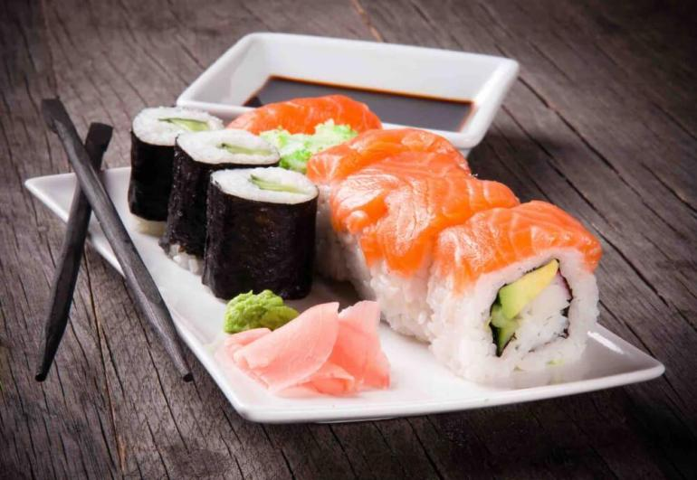 Find out the best Japanese restaurants in Maui Hawaii by top Hawaii blog Hawaii Travel with Kids. Image of a plate of sushi, chopsticks, and a dish of soy sauce.