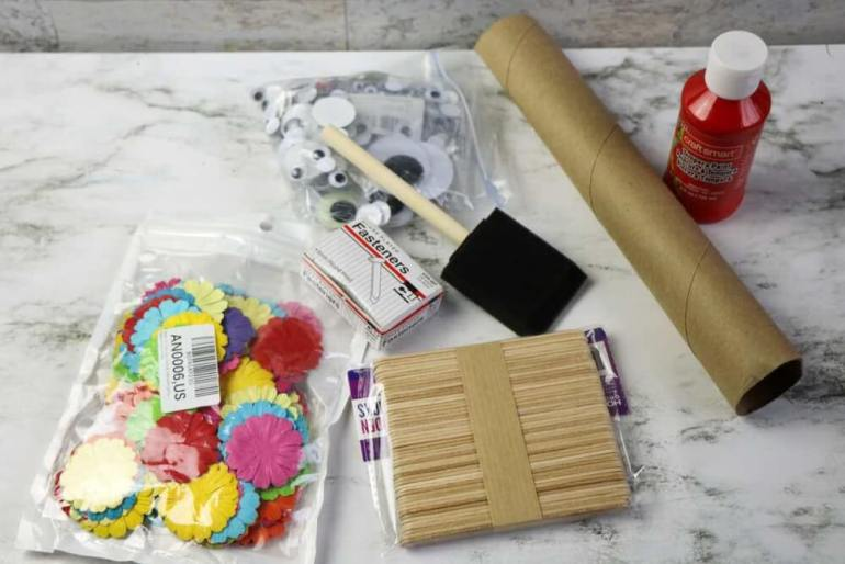 Here's what you need to make Chinese dragon puppets. Image of carboard tubes, red paint, ribbon, silk flowers, googly eyes, brads, and more.