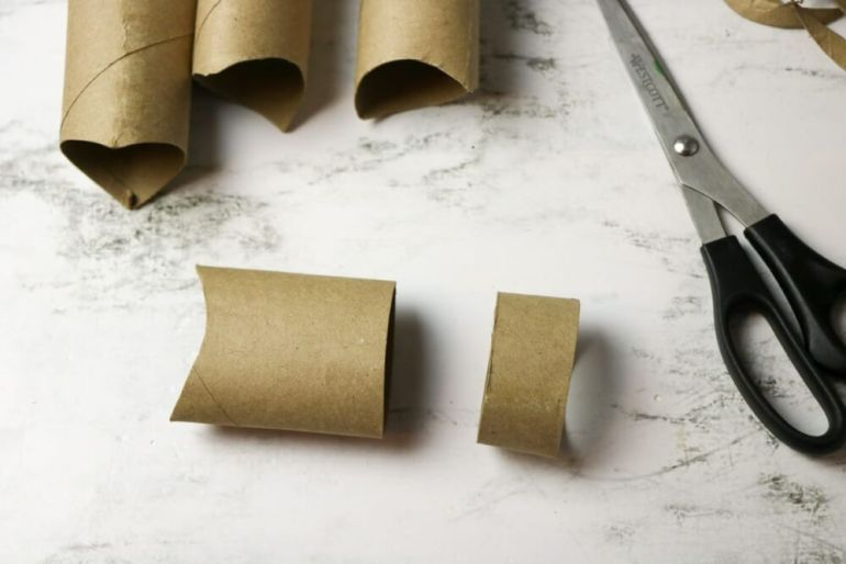 Cut one of the cardboard pieces into 2 smaller pieces. Image of a cardboard tube cut into pieces.