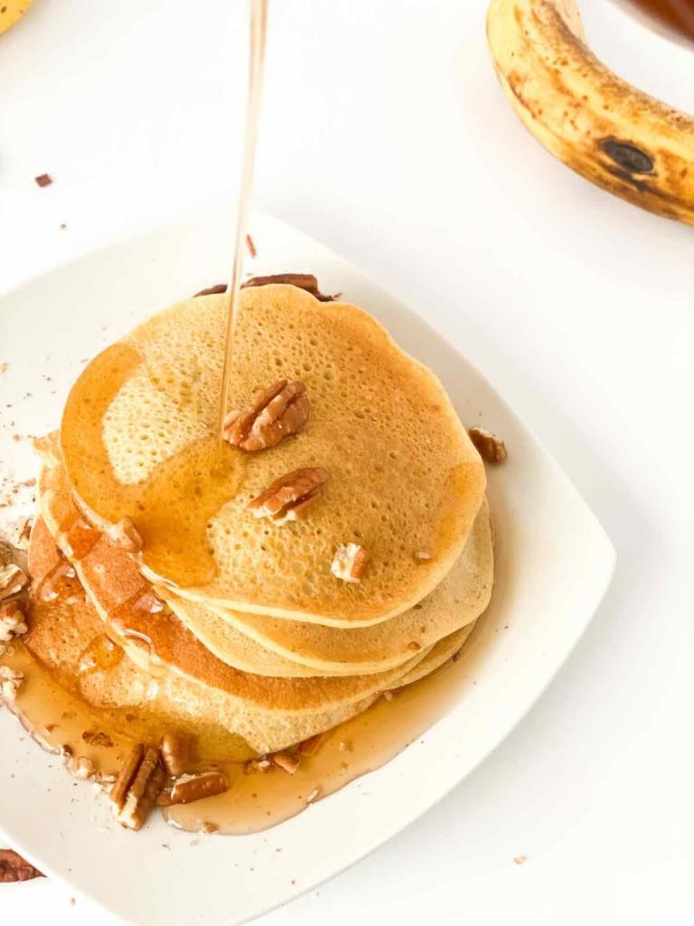 You can serve these gluten free dairy free banana pancakes with pure maple syrup and nuts. Image of someone pouring maple syrup on banana pancakes.