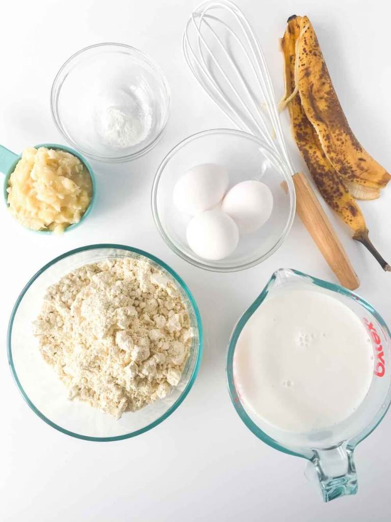 These are the banana pancakes gluten free ingredients you'll need. Image of mashed banana, gluten-free flour, eggs, baking powder, coconut milk, and salt.